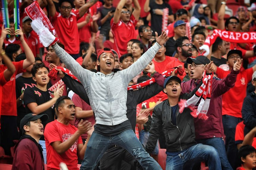 Above: Safuwan Baharudin's 12th-minute header opened the floodgates for Singapore, although the hosts were pegged back temporarily just a minute later by a Timor-Leste equaliser. Left: Home fans at the National Stadium had plenty to celebrate, with S