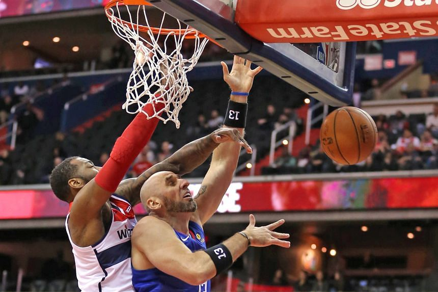The Los Angeles Clippers' Marcin Gortat (in blue) has his shot blocked by John Wall of the Washington Wizards during the first half at the Capital One Arena on Tuesday. The Wizards won the National Basketball Association game 125-118 to improve to 6-