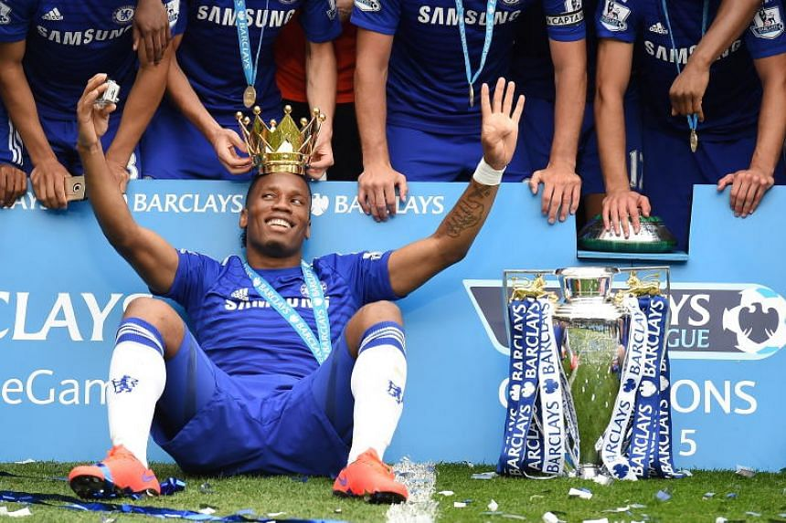 Didier Drogba celebrates with teammates the English Premier League winner's trophy at Stamford Bridge in London on May 24, 2015.