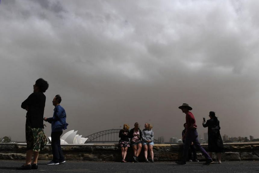 Tourists taking photographs against the backdrop of the Sydney Harbour as a dust storm descends on the city, on Nov 22, 2018.