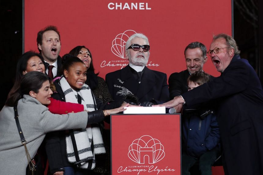 Lagerfeld (centre) presses a symbolic button to switch on the Champs-Elysees Christmas illuminations.