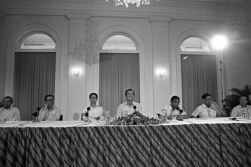 Above: Mr Goh Chok Tong with Mr Lee Hsien Loong at Mr Lee's swearing-in ceremony as prime minister at the Istana on Aug 12, 2004. Right: Mr Heng Swee Keat (far right) and Mr Chan Chun Sing with students in 2012. Mr Heng is set to be named the People'