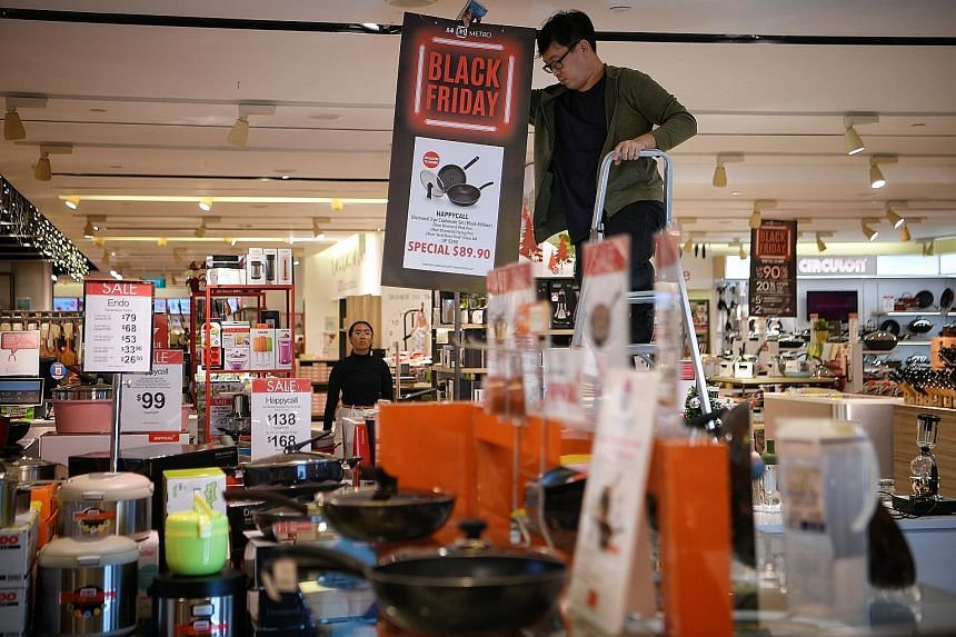 Promotional signs being put up as Metro geared up for the Black Friday sale at its Centrepoint store yesterday. The retailer is opening at 7.30am today, and offering discounts of up to 90 per cent. The queue outside Robinsons at The Heeren at around