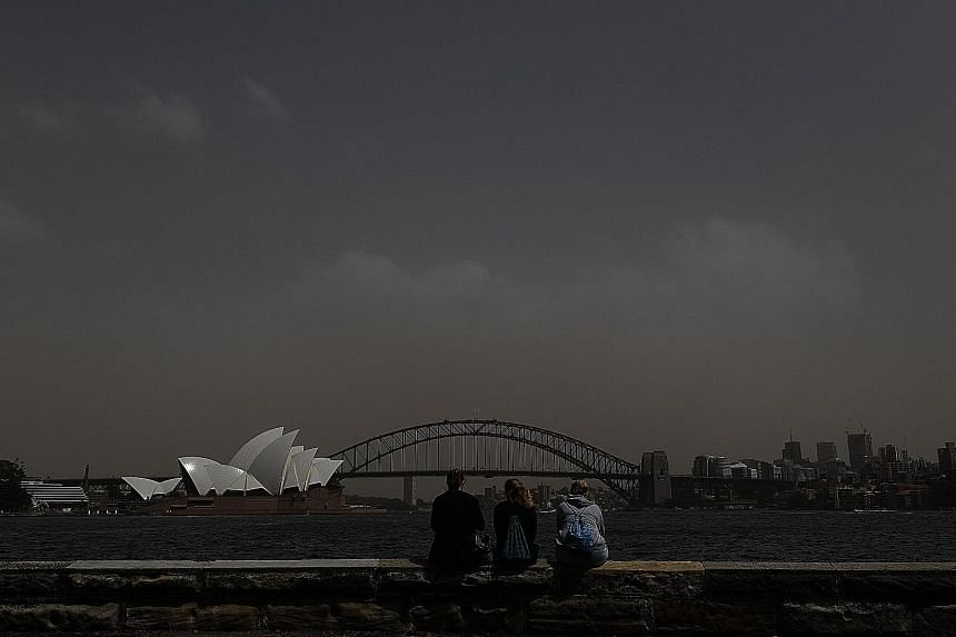 People taking photographs of the Sydney skyline, including the Harbour Bridge and Opera House, as a dust storm descended on the capital of New South Wales yesterday, prompting warnings over air quality. Australia is the driest inhabited continent on