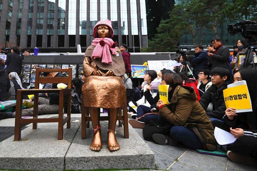 """South Korean protesters sit near a statue of a teenage girl symbolising former """"comfort women"""", during a weekly anti-Japanese demonstration in front of the Japanese embassy in Seoul, on Nov 21, 2018."""