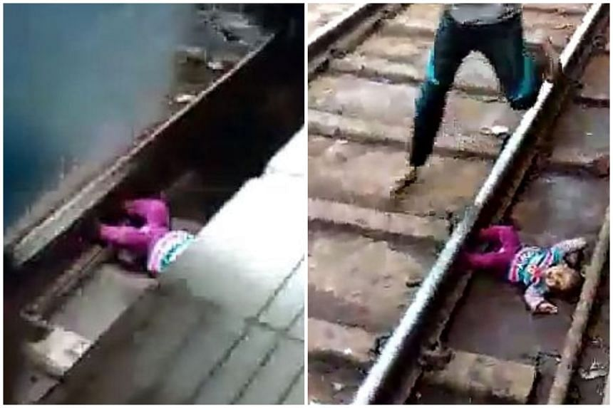 Cellphone footage showing the baby lying in the gap between the train carriage and platform in an Indian railway station.