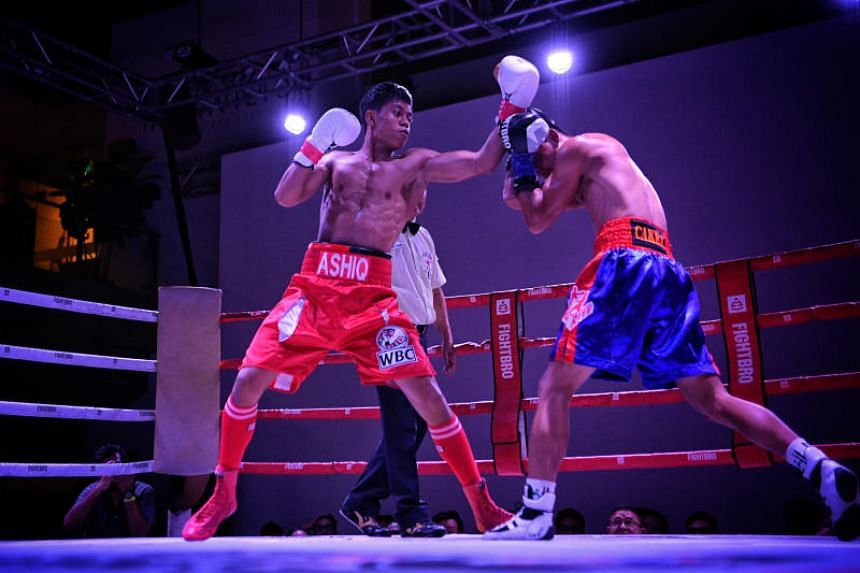 Singaporean professional boxer Muhammad Ashiq (left) and Indonesian Galih Susanto in action during the World Boxing Council (WBC) International Silver super bantamweight (up to 55kg) title at the Lion City Fury event held on Nov 23.