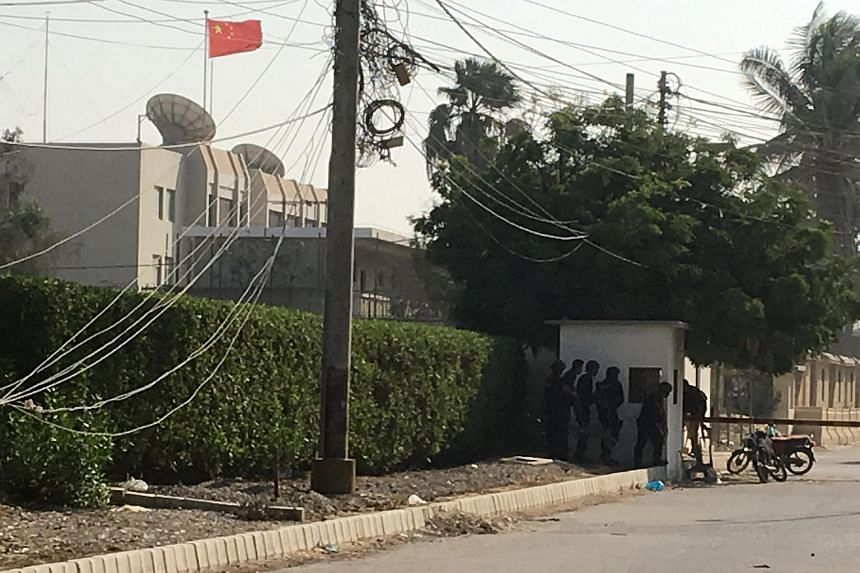 Paramilitary forces and police take cover behind a wall during an attack on the Chinese consulate, where blasts and shots are heard, in Karachi, Pakistan on Nov 23, 2018.