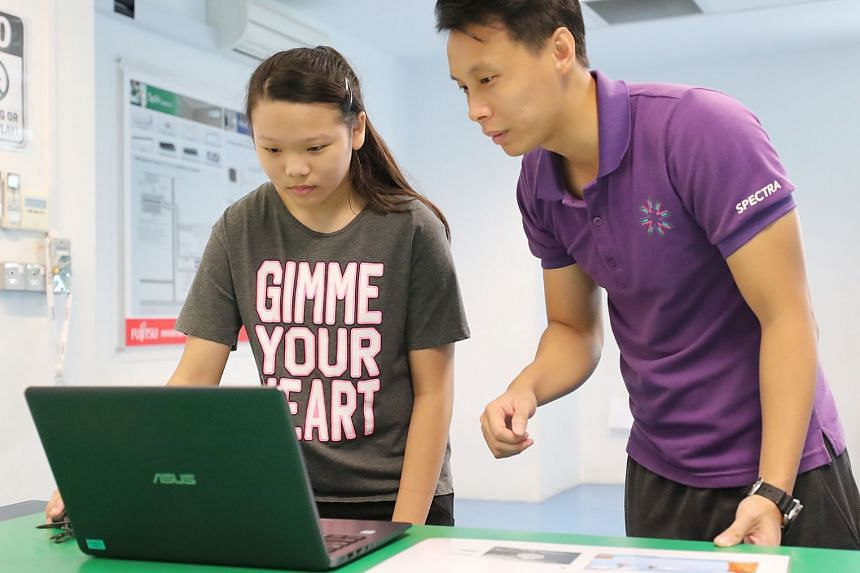 Mr Aaron Poh, 32, a vocational education teacher in Spectra Secondary School, showing Sharon Tan the websites and games she will learn to design if she enrols in the school. This will be under the mobile Web applications course. From left: Sisters Sh