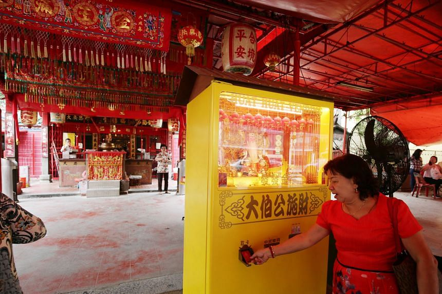 Devotee Teo Mui Kheng, 63, using the 4-D vending machine at the Goh Chor Tua Pek Kong temple. All she has to do is put money into the vending machine which, in return, will spit out a card with 4-D numbers.