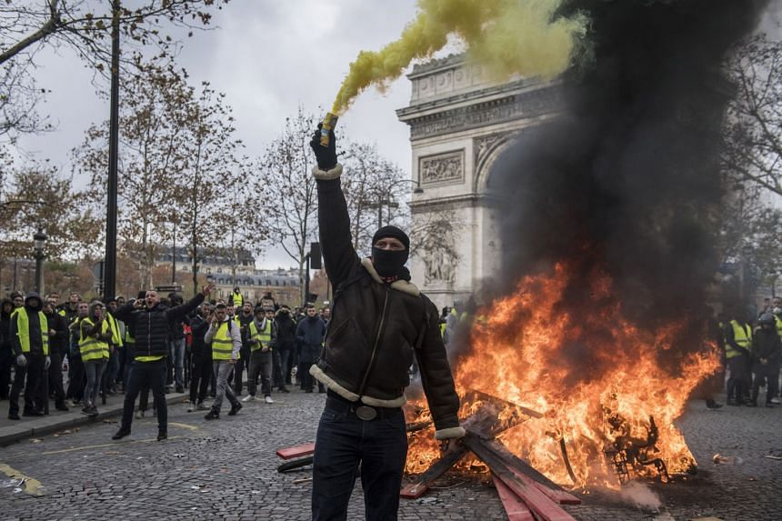 Protesters wearing yellow vests, as a symbol of protest against higher fuel prices, riot on the Champs Elysee.
