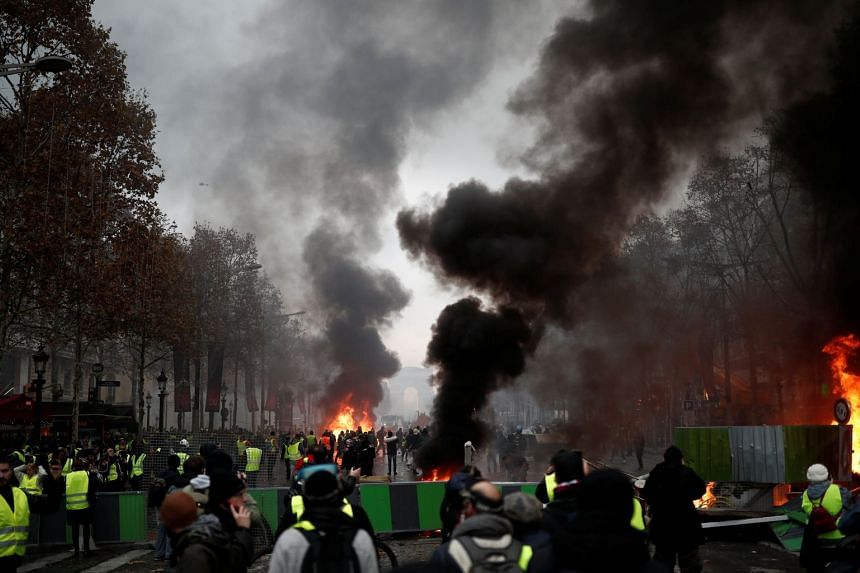 Protesters wearing yellow vests, a symbol of a French drivers' protest against higher fuel prices, stand in front of the barricade during riots on the Champs-Elysees.