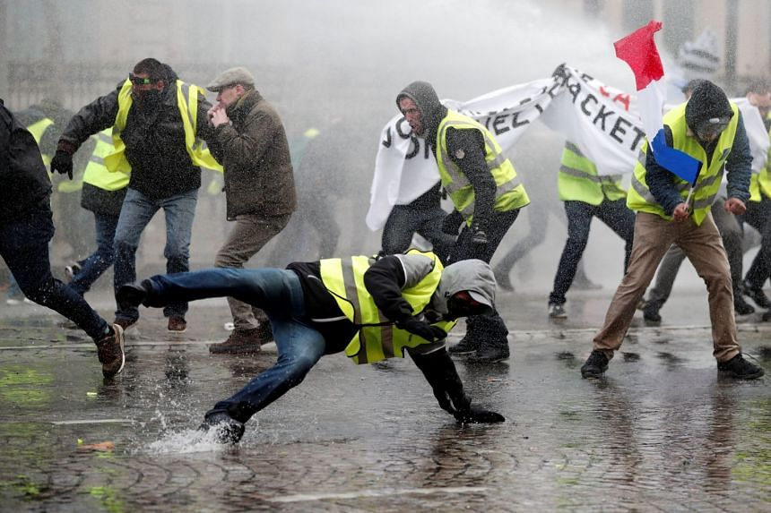 Protesters wearing yellow vests, a symbol of a French drivers' protest against higher fuel prices, face a water canon fired by police during clashes on the Champs-Elysees.