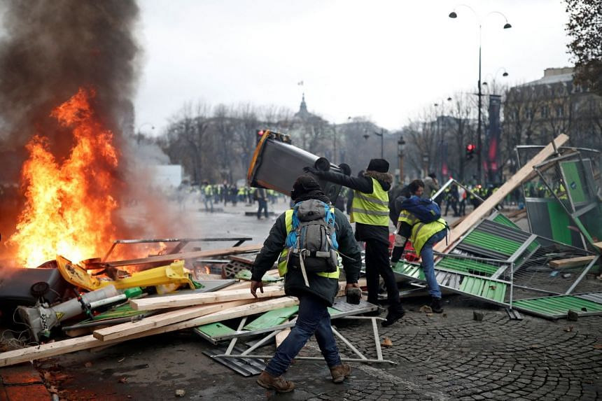 Protesters wearing yellow vests, a symbol of a French drivers' protest against higher fuel prices, make a barricade during riots on the Champs-Elysees.
