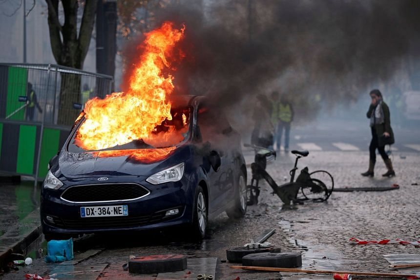 "A car is set ablaze during riots at a ""yellow vest"" protest on the Champs-Elysees."