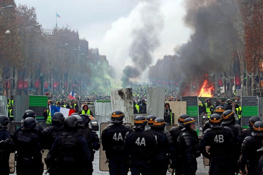 Protesters wearing yellow vests, a symbol of a French drivers' protest against higher fuel prices, shout slogans at police during riots on the Champs-Elysees.