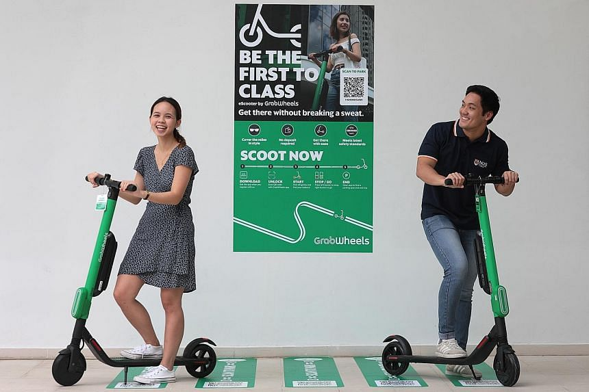 NUS students Melodie Claire Wong and Nicholas Tey with the GrabWheels e-scooters. There are eight GrabWheels parking stations at the school's Kent Ridge campus, and Grab aims to increase the number of such stations to 30 by the year end.