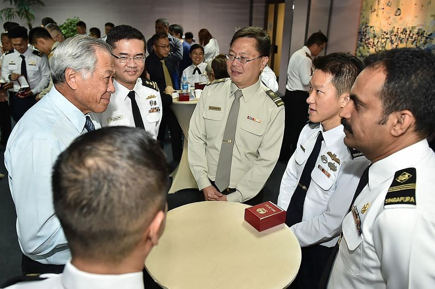"""Colonel Saw Shi Tat said cultivating the """"family spirit"""" within the team was something that was planned months before their deployment. Defence Minister Ng Eng Hen (far left) and Chief of Navy Rear-Admiral Lew Chuen Hong (second from left) chatting w"""