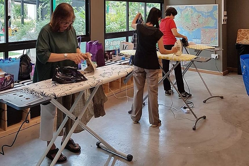 Left: Mr Darren Wong, founder of The Social Iron, which pays seniors for ironing services. Above: Madam Lum Lili (left) practising her ironing with other members at Sasco's Senior Activity Centre in Compassvale. She joined The Social Iron after readi