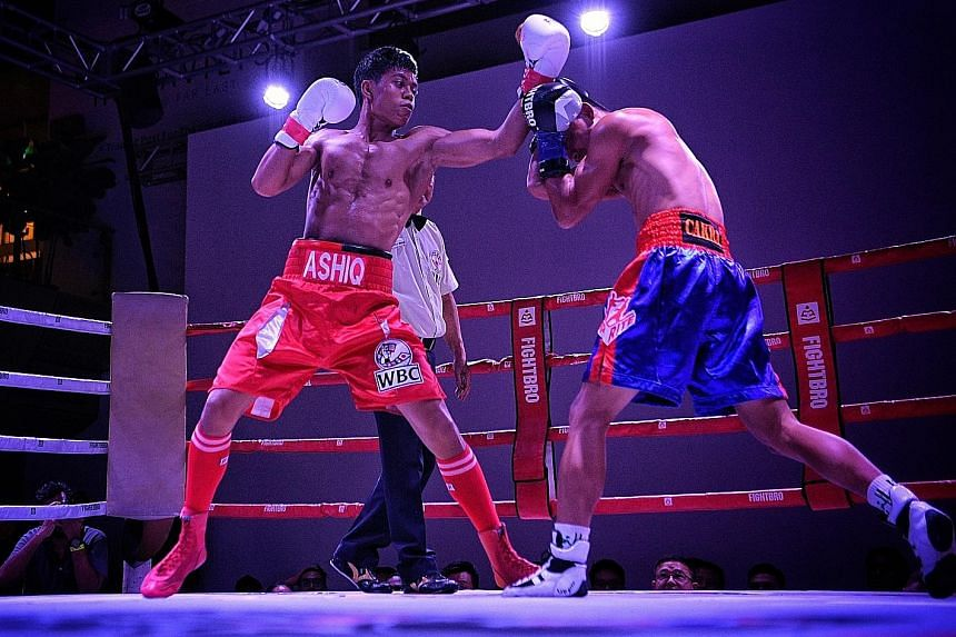 Singapore's Muhammad Ashiq (left) landing a left on Indonesian Galih Susanto during their World Boxing Council International Silver super bantamweight title bout yesterday.