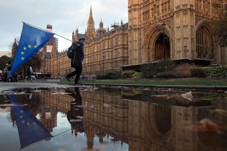 """An anti-Brexit protester with an EU flag outside the Houses of Parliament in London on Wednesday. Britain faces """"more division and more uncertainty"""" if a draft Brexit deal falls through, said British Prime Minister Theresa May as she sought to win ov"""