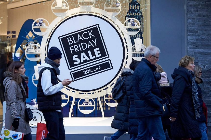 Shoppers on London's Oxford Street pass a promotional sign for Black Friday sales discounts.