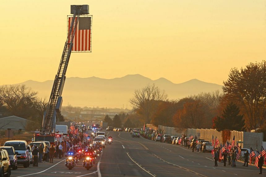Motorcycle officers escort the hearse carrying the remains of Utah National Guard Maj. Brent Taylor past City Hall in North Ogden, Utah on Nov 14, 2018.