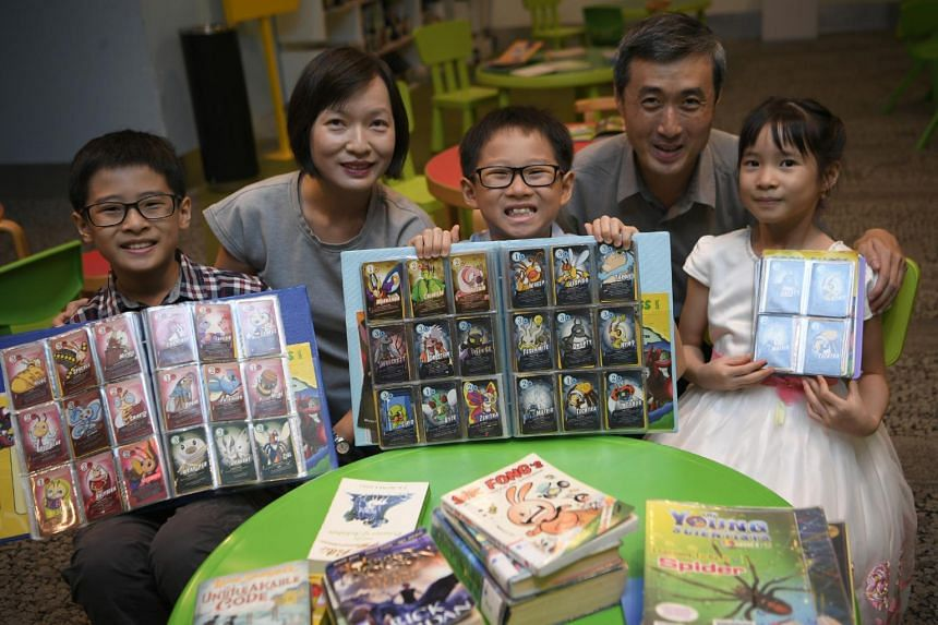 Ms Joanne Lee, her husband and their three children with their Book Bugs cards. The Book Bugs reading programme by the National Library Board has become a hit.