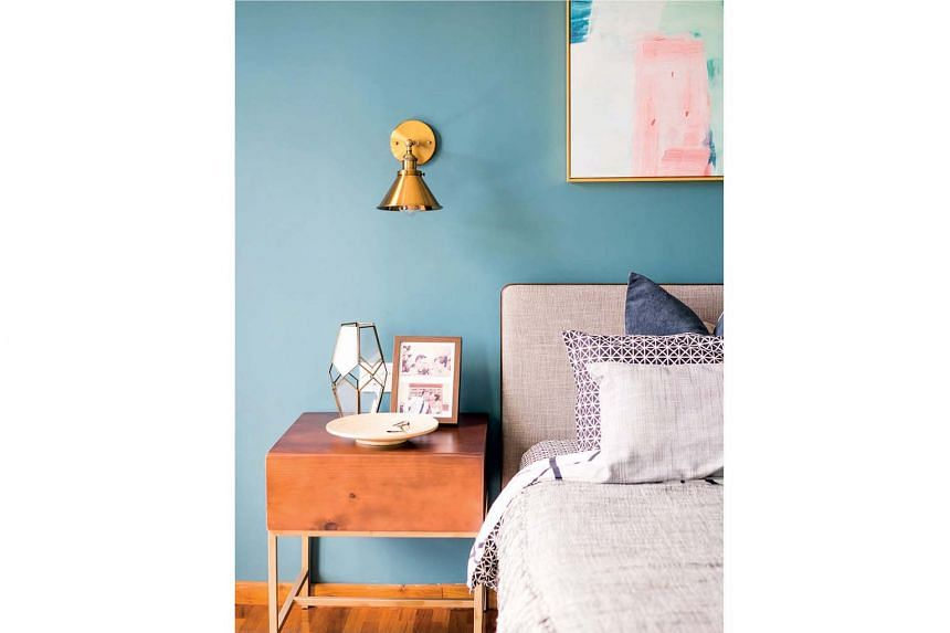 The master bedroom has a more adventurous palette and styling, from elegant drapes to ornate lighting fixtures, including a gold sconce lamp (above) against the blue wall.