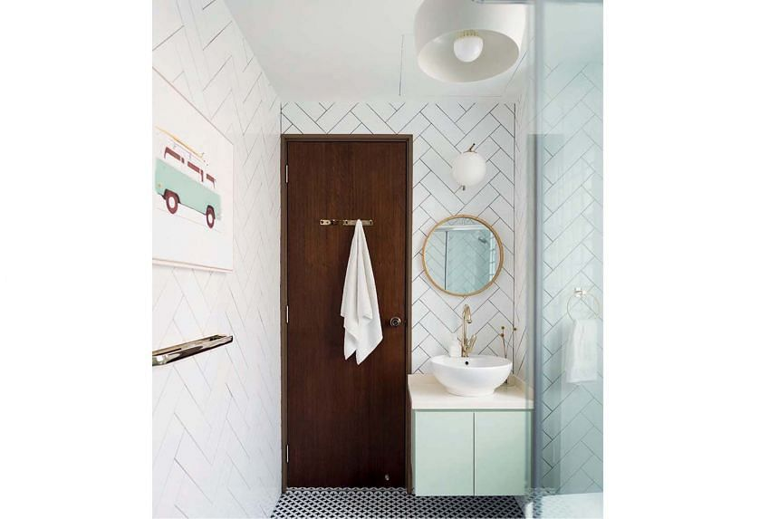 The wall tiles in the bathroom are laid in a herringbone pattern.
