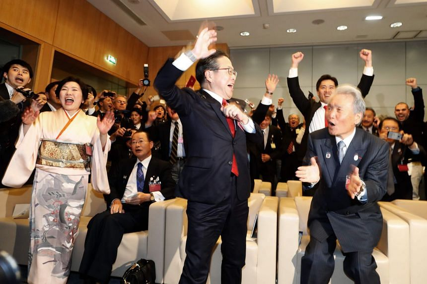 Japanese Economy minister Hiroshige Seko (centre) and members of the Japan delegation celebrate.