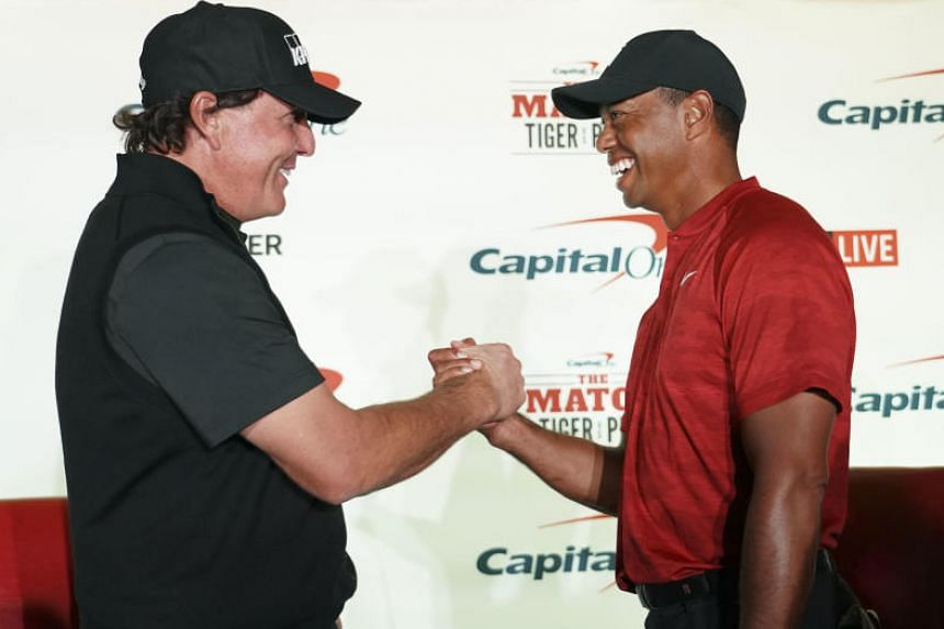 Phil Mickelson (left) and Tiger Woods shake hands during a press conference on Nov 20, 2018.