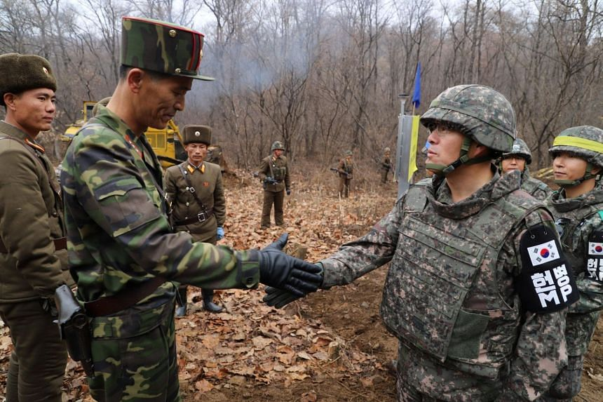 A South Korean military officer (right) and a North Korean military officer shake hands during an operation to reconnect a road across the Military Demarcation Line inside the Demilitarised Zone separating the two Koreas on Nov 22, 2018.