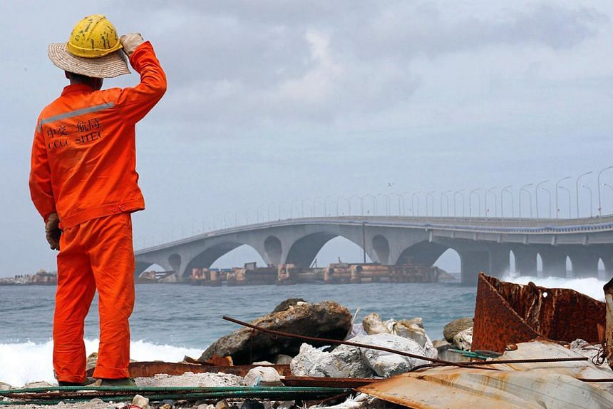 A construction worker looks on as the China-funded Sinamale bridge is seen in Male, Maldives on Sept 18, 2018.
