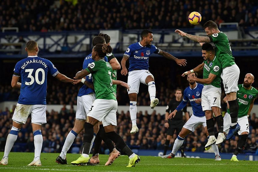 Watford's French midfielder Younes Kaboul (second from right) heads the ball celar of Everton's English striker Theo Walcott (centre) during the English Premier League football match between Everton and Brighton and Hove Albion at Goodison Park in Li