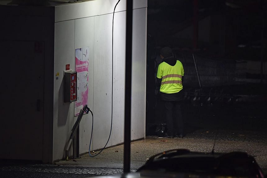 A man wearing a yellow vest stands as police carry out an intervention at the car wash station of the Espace Anjou shopping centre in Angers, France, on Nov 23, 2018.