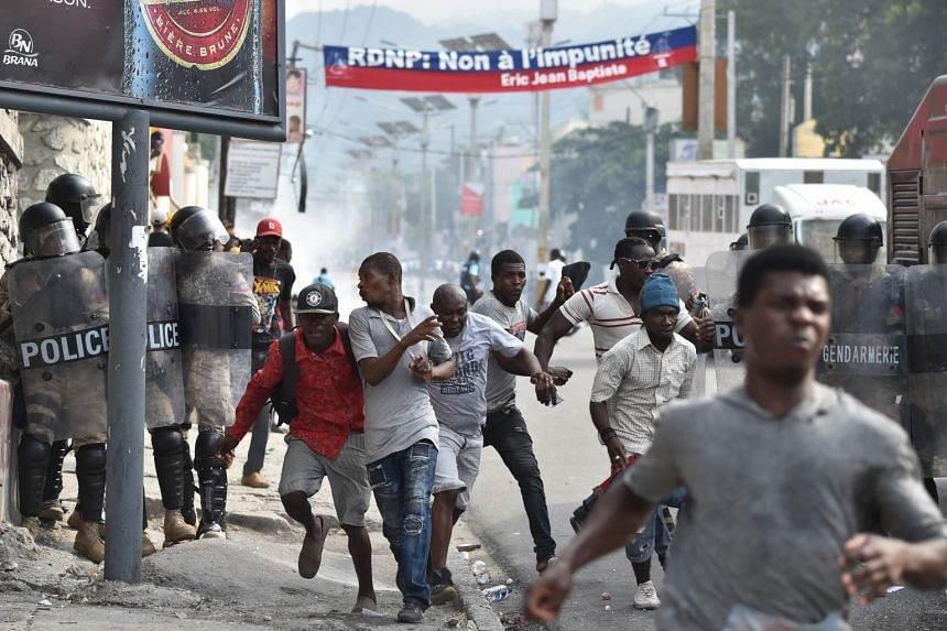 Protesters and pedestrians flee tear gas thrown by the Haitian police during a march through the streets of Port-au-Prince, on Nov 23, 2018.