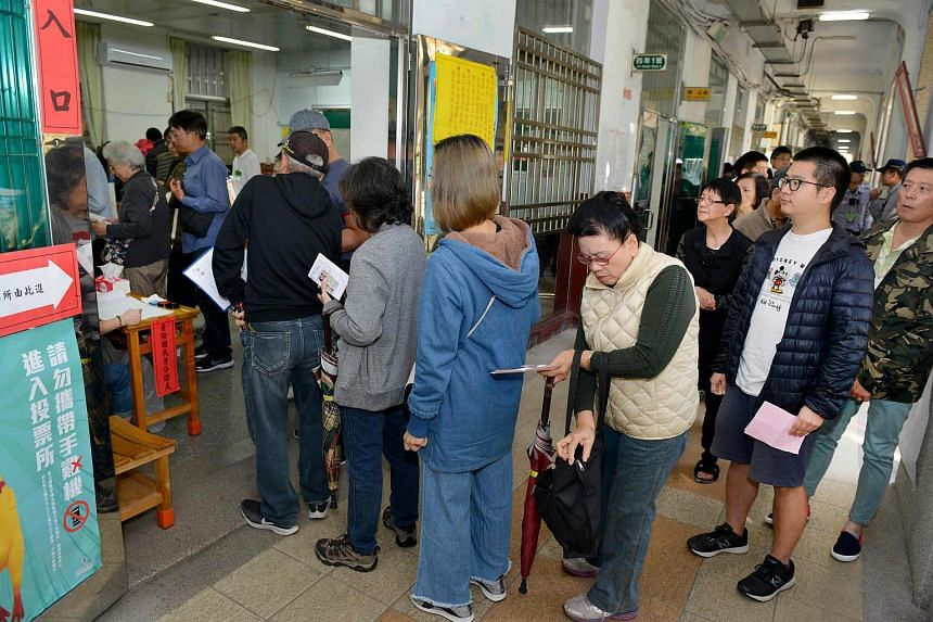 Residents queue outside a polling station at an elementary school to vote in local elections in Taipei on Nov 24, 2018.