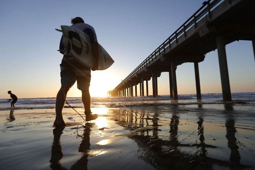 A surfer walks into the water beneath Scripps Pier on the Pacific Ocean in San Diego,