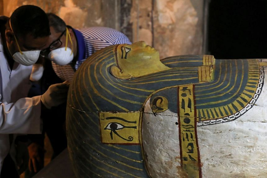 Egypt's Antiquities Minister Khaled El-Enany (second left) attends the unveiling of an intact sarcophagus.