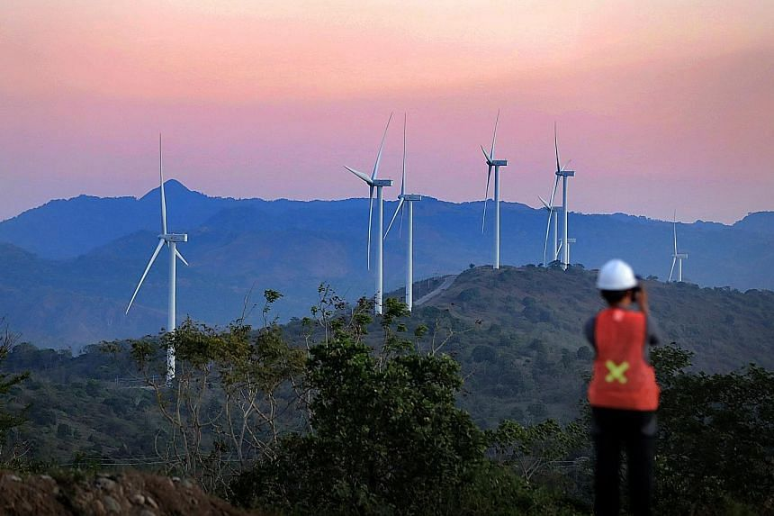Wind turbines at the Sidrap wind farm in Sidenreng Rappang regency, South Sulawesi. Hills and mountains make up 53 per cent of the 2,500 sq km regency, located as high as 3,086m above sea level. A child taking a peek as sugarcane farmer Sundinge, 35,