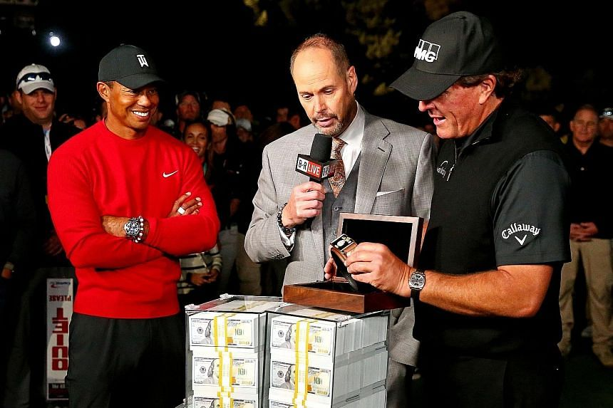 Phil Mickelson picking up the winner's belt and US$9 million after beating Tiger Woods on Friday.