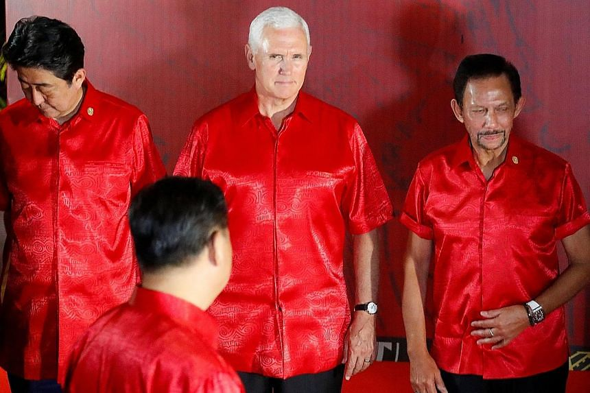 US Vice-President Mike Pence, flanked by Japan's Prime Minister Shinzo Abe (left) and Brunei's Sultan Hassanal Bolkiah, faces Chinese President Xi Jinping (back to camera) as they prepare for a group photo at a gala dinner during the Apec summit in P