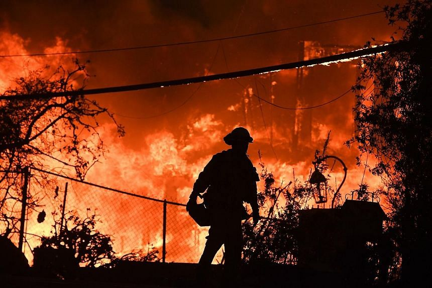 A firefighter outside a burning home during the Woolsey Fire in Malibu, California, early this month. The latest edition of the US National Climate Assessment lays out the devastating effects of a changing climate on the economy, health and environme