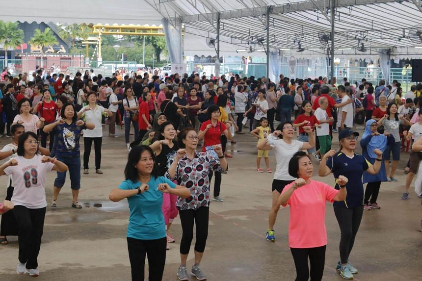 Seniors taking part in a mass zumba session by the Health Promotion Board at the active ageing carnival in Sembawang, on Nov 25.