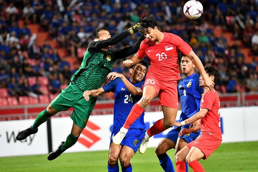 Thai goalkeeper Chatchai Budprom punching away a header from Singapore's Ikhsan Fandi in the AFF Suzuki Cup match in Bangkok on Nov 25, 2018.
