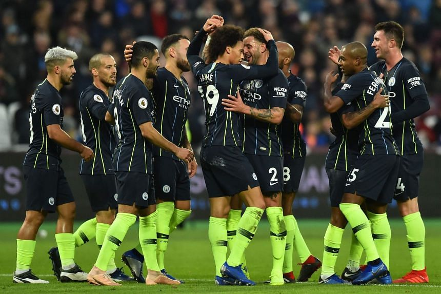 Manchester City's Leroy Sane (centre) celebrates with team-mates after scoring their third goal.