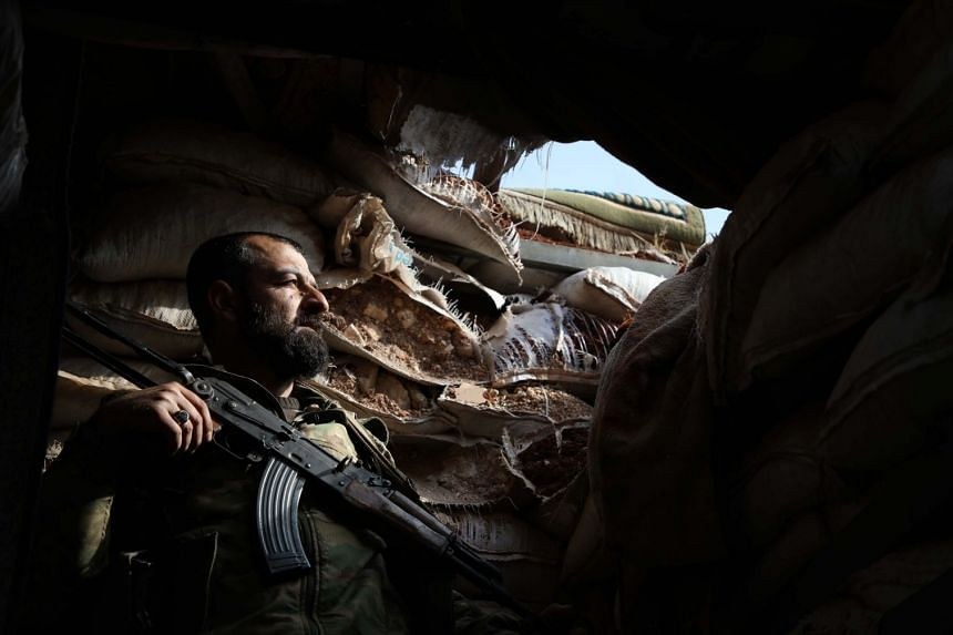 A Syrian rebel-fighter from the National Liberation Front takes position on the frontline facing government forces in the al-Rashedin area west of Aleppo in northwestern Syria, on Nov 20, 2018.