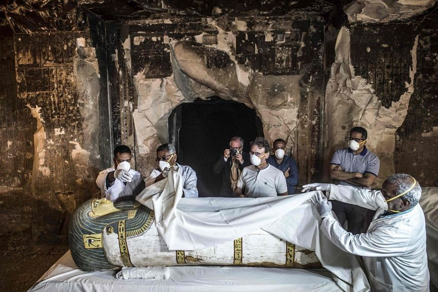 Egyptian officials inspect an intact sarcophagus during its opening at the site of Tomb TT33 at Al-Assasif necropolis.