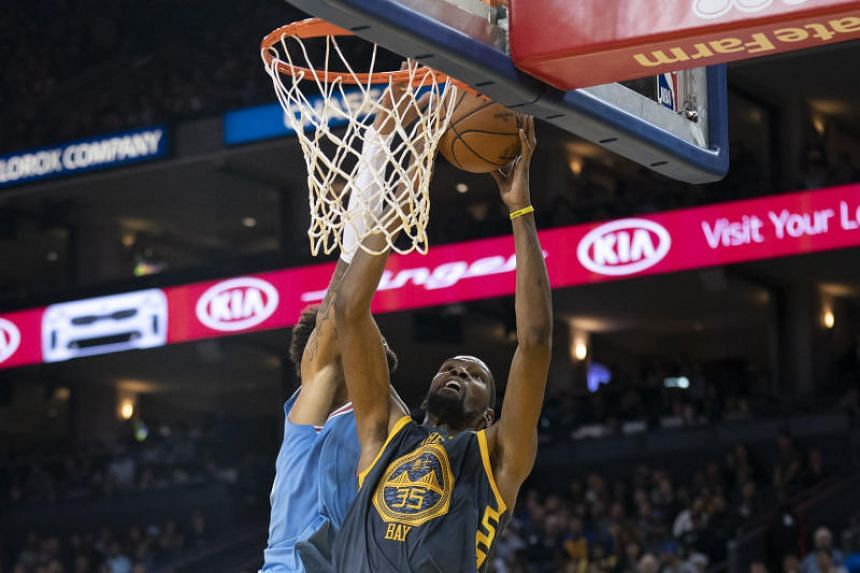 Golden State Warriors forward Kevin Durant (#35) going for a dunk against Sacramento Kings centre Willie Cauley-Stein during their NBA match on Nov 24, 2018.